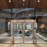 Contemporary glass entrance door set in structural glass walls