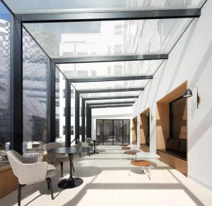 Office meeting space with structural glass walls and roof and steel industrial look beams