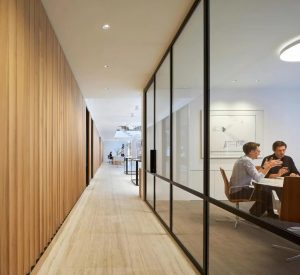 Office meeting room with structural glass walls and industrial style steel frames