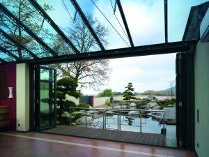 Glass roofed conservatory with open bifold doors looking out onto water garden feature