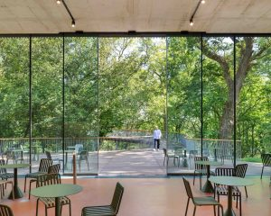 Floor-to-ceiling minimal framed double-height sliding glass entrance doors to story of gardening museum