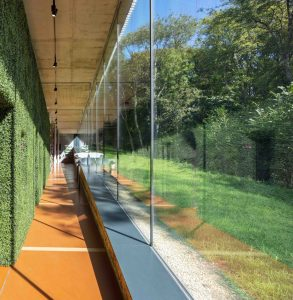 Double-height oversized frameless structural glass wall at story of gardening museum