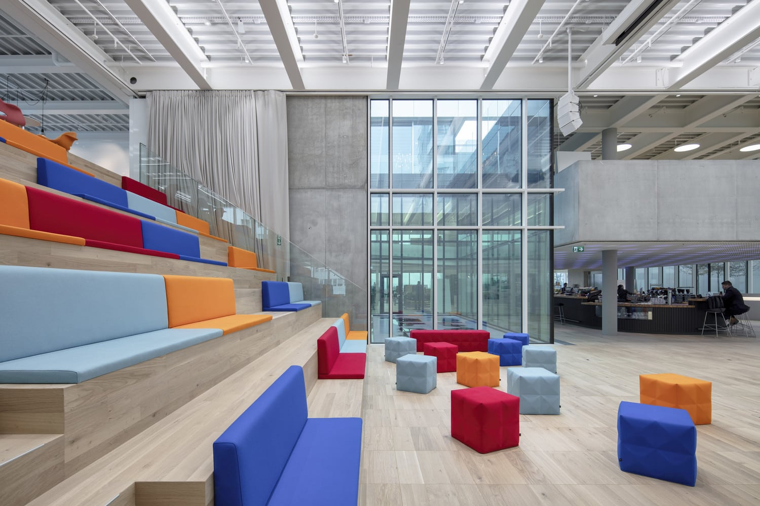 Modern office meeting space with colourful seats and frameless glass walls