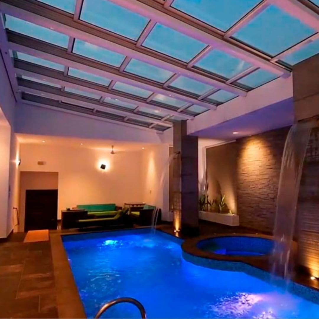 luxury outdoor swimming pool covered by a retractable glass roof to make a pool that can be used in any weather