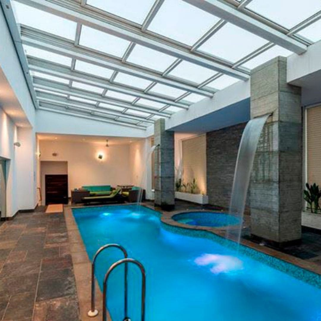 retractable glass roof covering a luxury swimming pool area so the roof can be opened to give the pool and outdoor feel