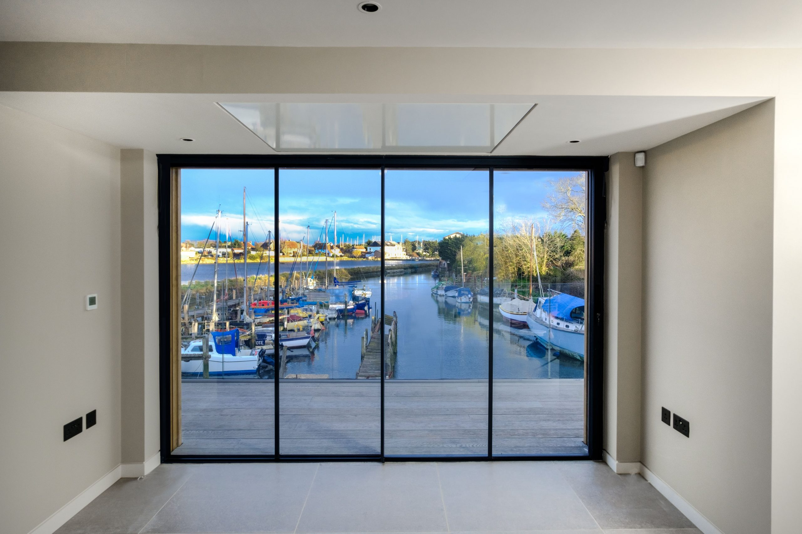 floor to ceiling aluminium sliding windows on a contemporary waterfront residential development
