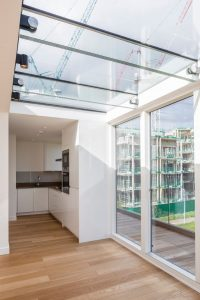 innovative rooftop glass extension on modern apartment block