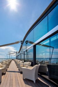 large curved glass wall with views of the sea