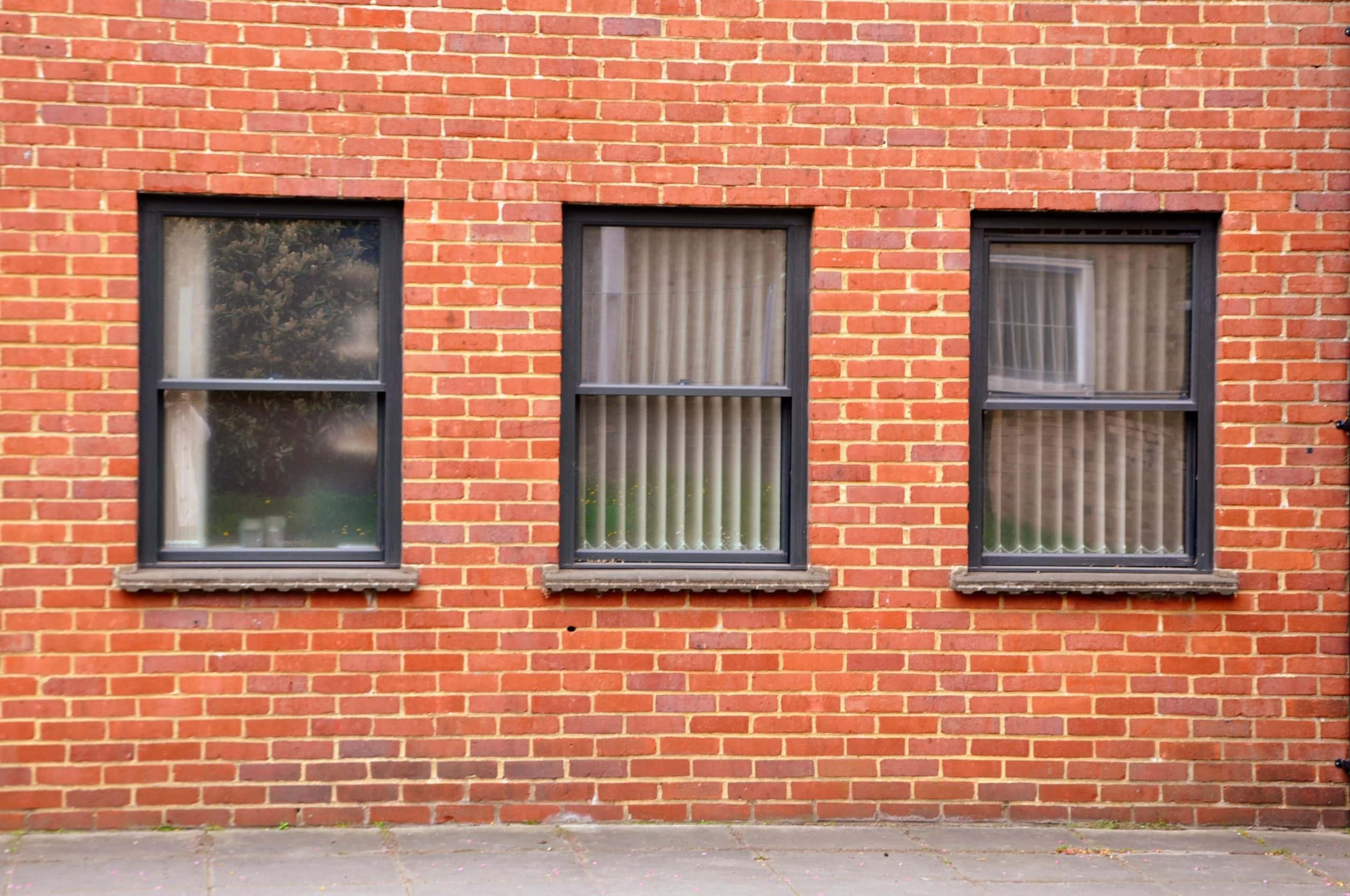 three traditional style windows complementing traditional red brick work