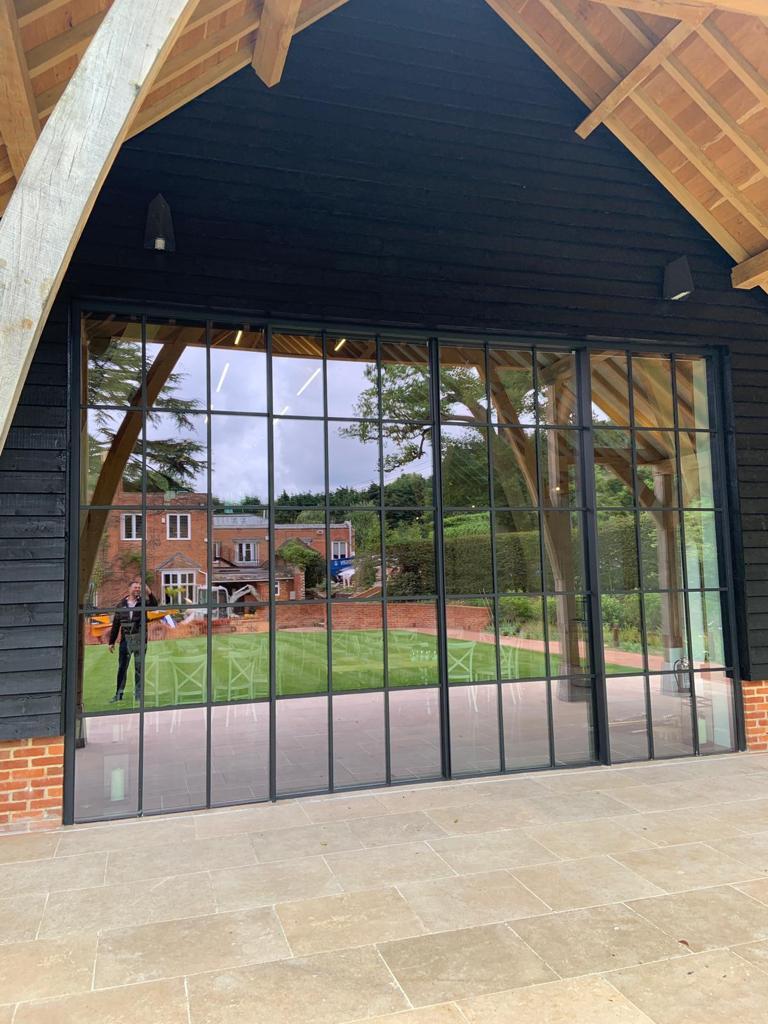 triple glazed aluminium sliding glass doors with glazing bars for a steel look design