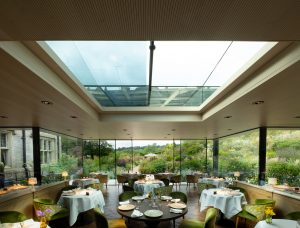 electric sliding rooflight and sliding glass walls in a restaurant glass extension