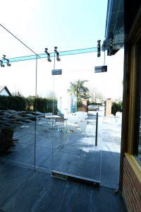 frameless glass lobby installed on the dog and badger restaurant