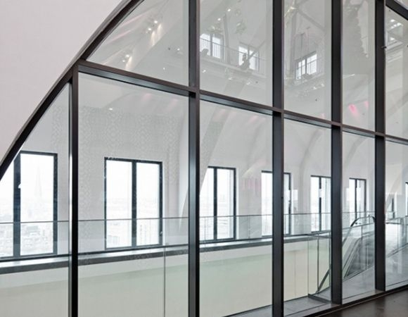 a commercial space with large steel framed fire rated glass partition
